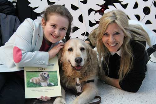 Evelina London patient, Amelie, Nala the dog and CBBC presenter Naomi Wilkinson pose with the Evelina London Pet Book
