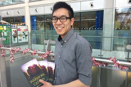 Adrian Li holds up his book, The Warriors of Genesis