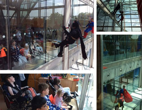 Window cleaner dressed in superhero costumes at Evelina London
