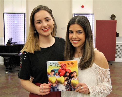 Hannah and Katie, authors of the pacemaker guide for teenagers, holding the booklet between them and smiling