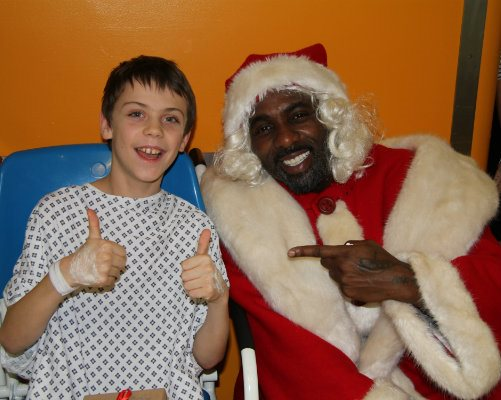 Idris Elba dressed as Father Christmas with boy