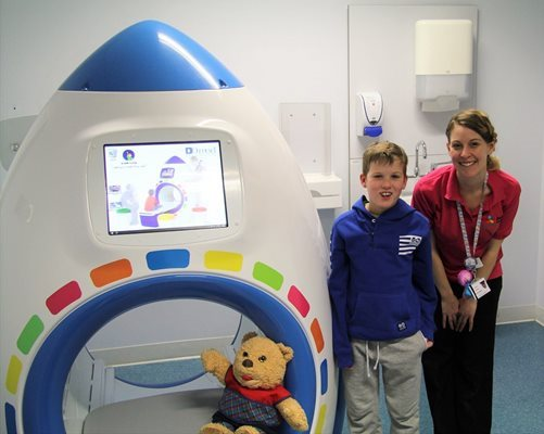Young boy and play specialist with play MRI scanner