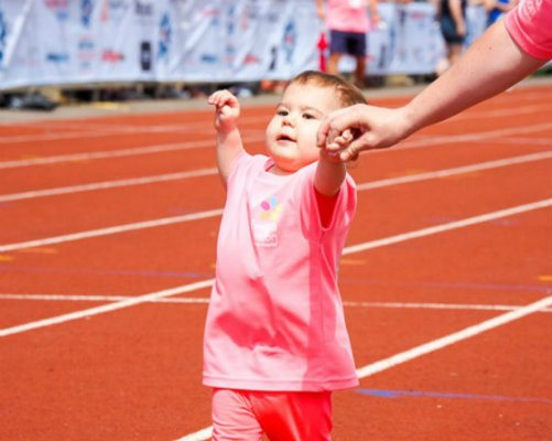 Mia on a running track holding her mum's hand during the British Transplant Games.