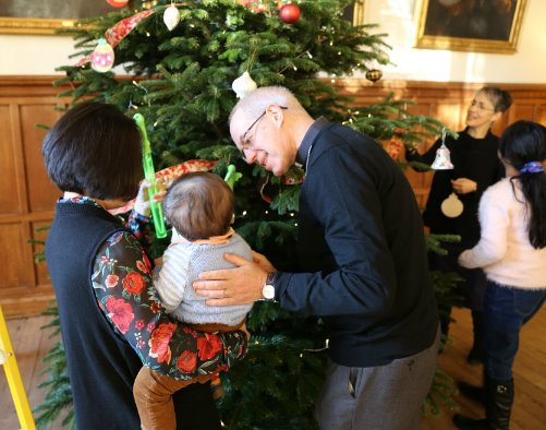 The Archbishop of Canterbury, Justin Welby, with a family next to a large Christmas tree in Lambeth Palace