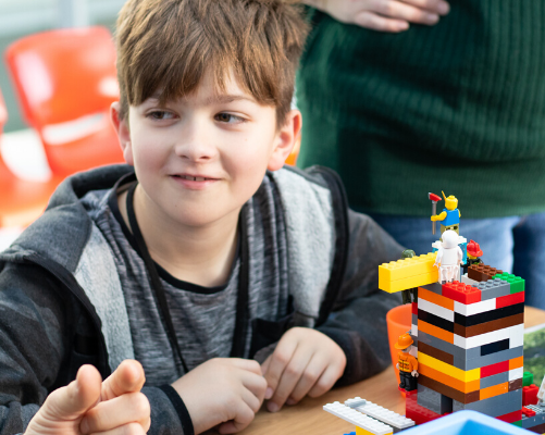 A boy building a lego tower and smiling