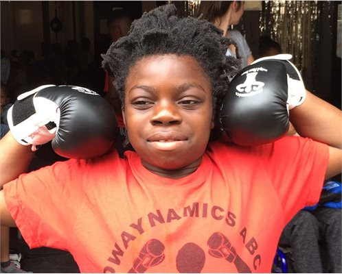 Young boy posing wearing boxing gloves