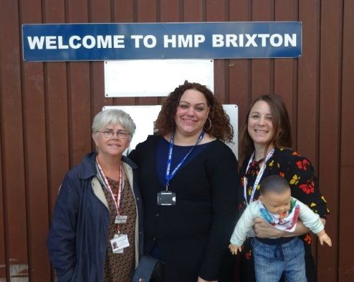 "A group of professionals from Evelina London beside a sign that reads ""Welcome to HMP Brixton"" and a doll which is used in training."