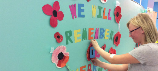 Tilly making adding paper poppies to a display for rememberance day that reads we will remember.