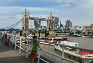 Munkh in central london standing by the Thames with bridges and boats behind him.