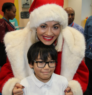 Rita Ora wearing a santa hat with Munkh at Chritmas in Evelina London hospital