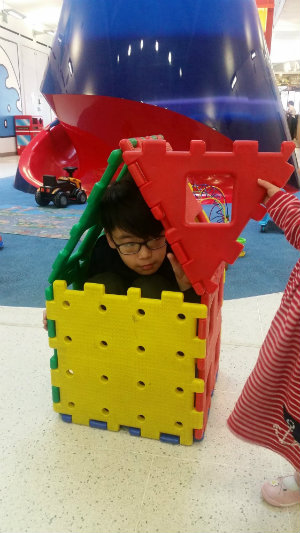 Munkh playing inside a tiny toy house