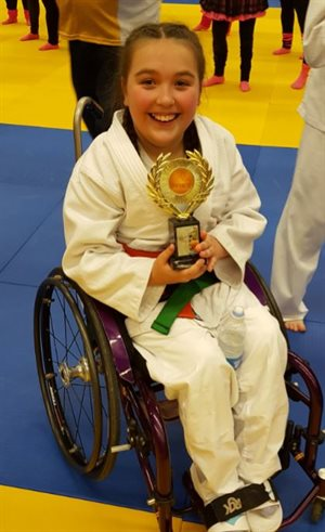 Isabelle wearing her judo uniform and holding a trophy