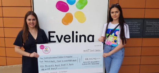 Amelia and her friend outside the Evelina London sign with a large cheque