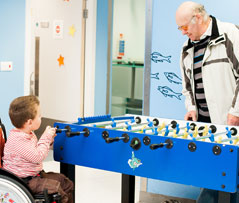 Boy in wheelchair playing table football with grandparent