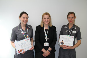 Two Evelina 150 stars holding their certificates with Miranda Jenkins, Director of Strategy