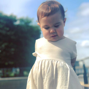 Mia, age 3, standing outside in a white dress on a sunny day.