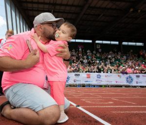 Mia hugging her dad after crossing the finishing line at the Briitsh Transplant Games.