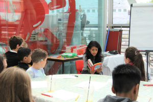 Konnie Huq reading her book to a group of patients