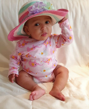 One-year-old Sayanna wearing a pink outfit and a colourful hat.