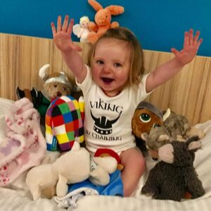 Evie Cox smiling with her hands up in the air and lots of toys.