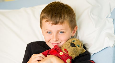 Boy in hospital bed with teddy