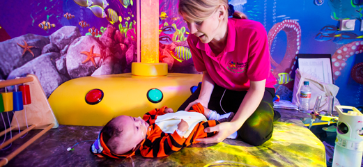 Play specialist and baby in sensory room